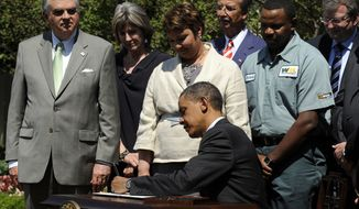 **FILE** President Obama signs a presidential memorandum outlining the next steps for cleaner and more efficient vehicles on May 21, 2010, in the Rose Garden of the White House in Washington. From left: Transportation Secretary Ray LaHood, White House energy czar Carol Browner, EPA Administrator Lisa Jackson, Navistar Chief Executive Officer Daniel Ustian, Waste Management driver Anthony Dunkley and Daimler Trucks North America Chief Executive Officer Martin Daum. (Associated Press)