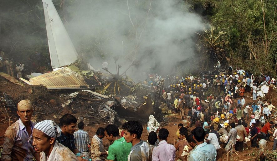 Civilians look on as Indian firefighters and rescue personnel gather around the site of an Air India plane that crashed in Mangalore, in the southern Indian state of Karnataka, Saturday, May 22, 2010. (AP Photo)