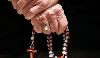 An elderly Maronite woman holds a rosary during Mass at Saint George's Cathedral in the Maronite Catholic village of Kormakitis in the remote northwestern tip of divided Cyprus. (Associated Press) ** FILE **