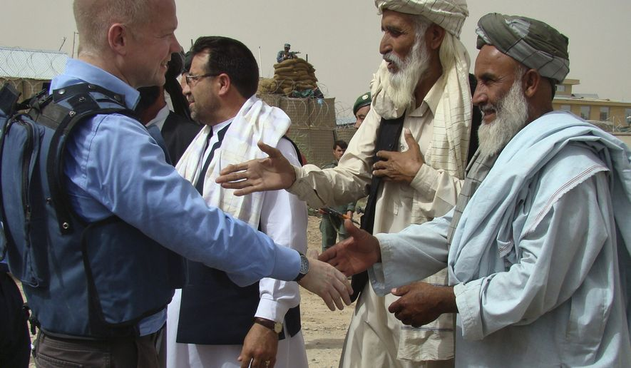British Foreign Secretary William Hague (left) shakes hands with Afghan elders during a visit to the Nad Ali district of Helmand province in southern Afghanistan on Sunday, May 23, 2010. (AP Photo/Abdul Khaleq)