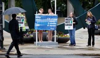 People for the Ethical Treatment of Animals backers demonstrate May 12 in Des Moines, Iowa. PETA has been buying stock in companies in an effort to influence animal-welfare policies. (Associated Press) ** FILE **