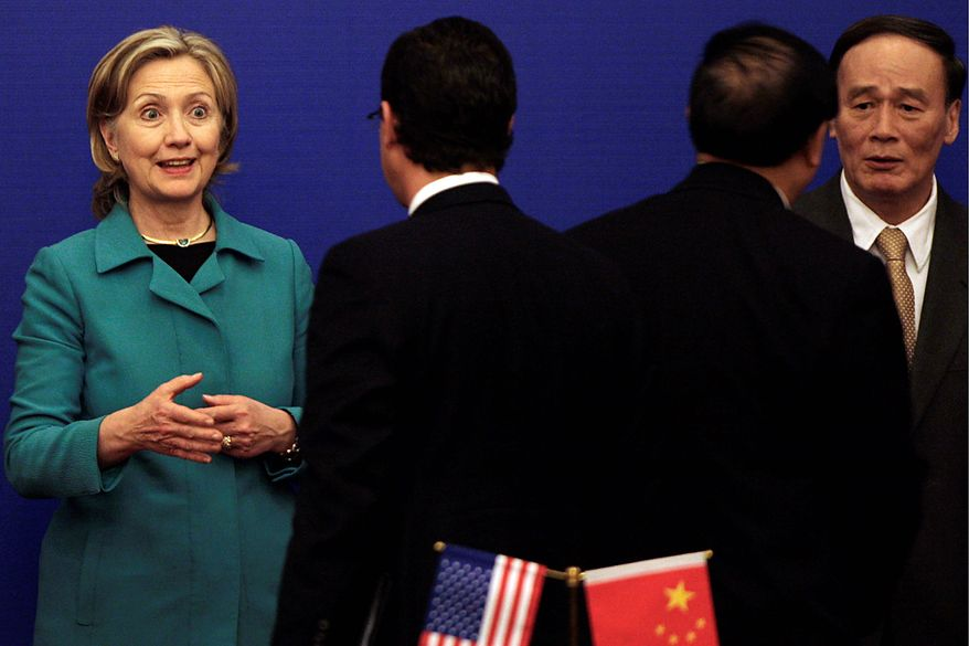 """Secretary of State Hillary Rodham Clinton (left) talks with a Chinese official during  a joint media conference with Chinese Vice Premier Wang Qishan (right) on the second round of the U.S.-China Strategic and Economic Dialogue at the Great Hall of the People in Beijing on Tuesday, May 25, 2010. Mrs. Clinton on Tuesday stepped up pressure on China to back international action against North Korea for the sinking of a South Korean warship, calling peace and security on the Korean peninsula """"a shared responsibility"""" between Washington and Beijing. (AP Photo/Muhammed Muheisen)"""