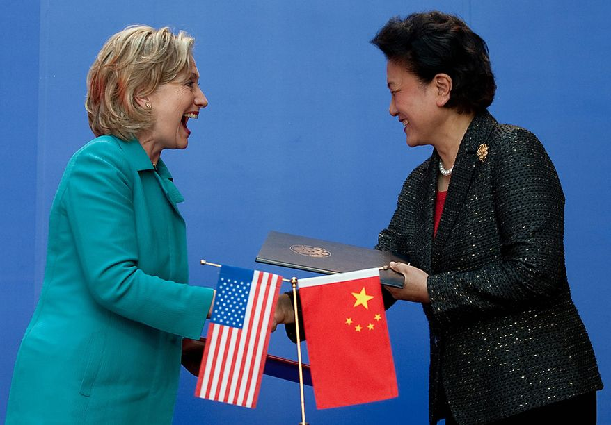 Secretary of State Hillary Rodham Clinton (left) shakes hands with Chinese State Councilor Liu Yandong after signing an agreement at the National Center for the Performing Arts in Beijing on Tuesday, May 25, 2010. (AP Photo/Saul Loeb, Pool)