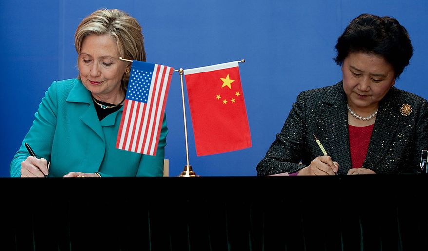 Secretary of State Hillary Rodham Clinton (left) and Chinese State Councilor Liu Yandong sign an agreement at the National Center for the Performing Arts in Beijing on Tuesday, May 25, 2010. (AP Photo/Saul Loeb, Pool)