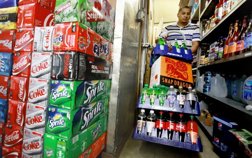 **FILE** Antonio Garcia restocks beverages at the Corner Market in Washington on May 22, 2010. (Associated Press)