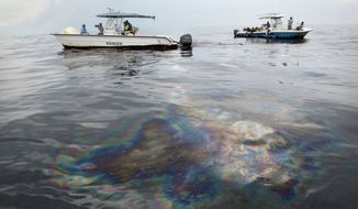 Oil shines of the surface of the Gulf of Mexico near the coast of Louisiana on Wednesday, May 26, 2010. (AP Photo/Jae C. Hong)