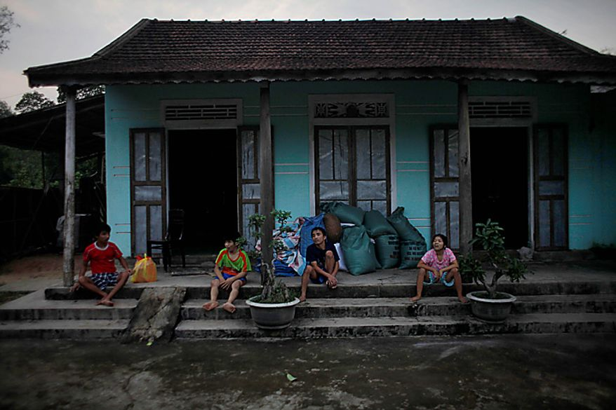 In this photo taken on Oct. 4, 2009, Vietnamese siblings, from left, Tran van Hoang, Tran Van Lam, Tran Van Luan and Tran Thi Luy, sit on the front porch of their family home in the village of Cam Tuyen, Vietnam. The siblings were born with profound physical and mental disabilities that the family, and local officials say, were caused by their parents' exposure to the chemical dioxin in the defoliant Agent Orange. (AP Photo/David Guttenfelder)
