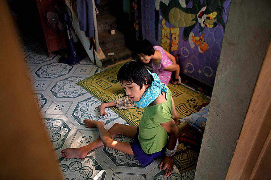 In this photo taken on Oct. 5, 2009, Son Nguyen Tri Lam, foreground, and his sister Nguyen Thi Hang sit inside their family home in the town of Cam Lo, Vietnam. Both had their hands tied behind their backs to prevent them from biting their arms and hands and seriously hurting themselves. The two siblings were born with profound physical and mental disabilities that the family, and local officials, say were caused by their parents' exposure to the chemical dioxin in the defoliant Agent Orange.  (AP Photo/David Guttenfelder)