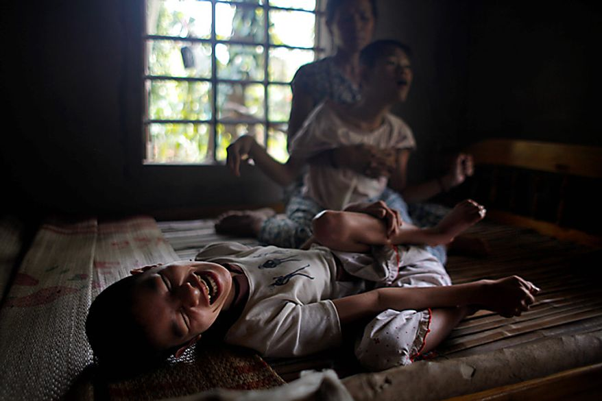 In this photo taken on Oct. 5, 2009, Tran Thi Gai, 45, comforts her daughter Nguyen Thi Tai, 21, while her youngest daughter Nguyen Thi Thuyet, 16, lies next to them on a bed in the village of Cam Tuyen, Vietnam. The two young women were born with profound physical and mental disabilities that the family, and local officials say, were caused by their parents' exposure to the chemical dioxin in the defoliant Agent Orange. (AP Photo/David Guttenfelder)