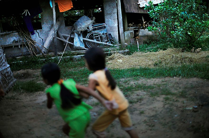 In this photo taken on Oct. 4, 2009, local children run past an old wheelchair sitting next to a chicken shed at the home of Tran Van Tram in the village of Cam Tuyen, Vietnam. Tran Van Tram and his wife have raised four children with profound physical and mental disabilities that the family, and local officials say, were caused by his parents' exposure to the chemical dioxin in the defoliant Agent Orange. (AP Photo/David Guttenfelder)