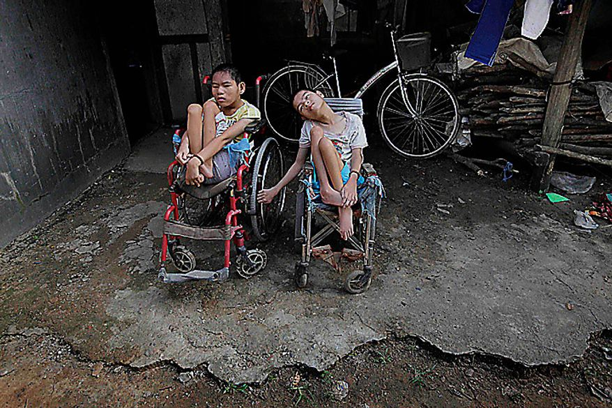 In this photo taken on Oct. 5, 2009, Nguyen Thi Tai, left, and Nguyen Thi Thuyet sit together in their wheelchairs outside their family home in the village of Cam Tuyen, Vietnam. The two young women were born with profound physical and mental disabilities that the family, and local officials say, were caused by their parents' exposure to the chemical dioxin in the defoliant Agent Orange. (AP Photo/David Guttenfelder)