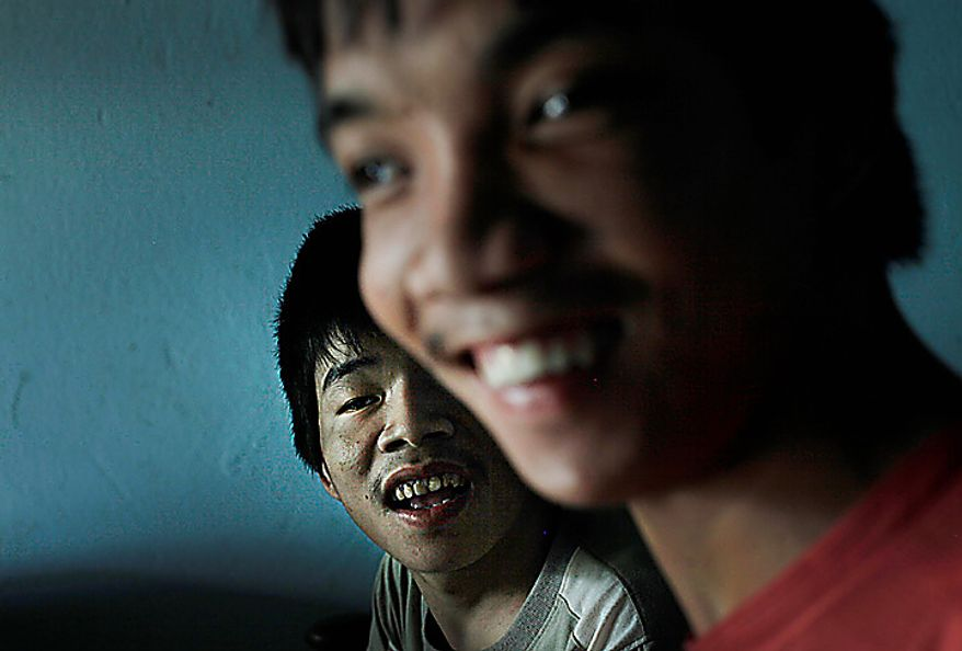 In this photo taken on Oct. 5, 2009, Tran Van Lam, left, and Tran van Hoang sit inside their family home in the village of Cam Tuyen, Vietnam. The two men were born with profound physical and mental disabilities that the family, and local officials, say were caused by their parents' exposure to the chemical dioxin in the defoliant Agent Orange. (AP Photo/David Guttenfelder)