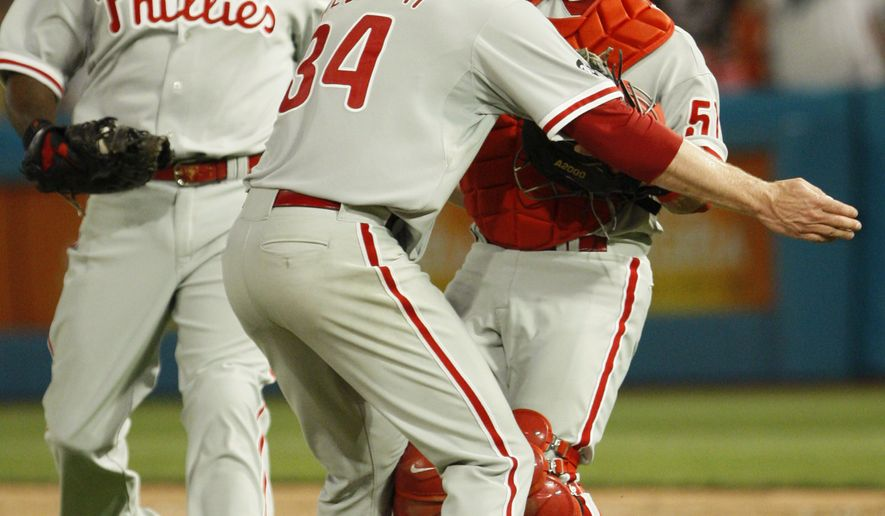 Philadelphia Phillies starting pitcher Roy Halladay, center, celebrates with Carlos Ruiz, right, and Ryan Howard after Halladay threw a perfect game during a baseball game against the Florida Marlins, Saturday, May 29, 2010 in Miami. The Phillies defeated the Marlins 1-0. (AP Photo/Wilfredo Lee)