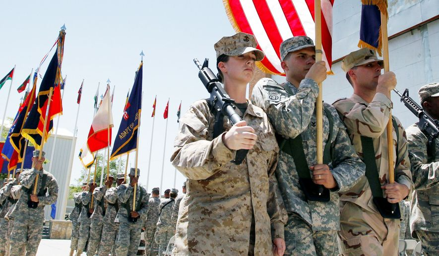 U.S. soldiers carry flags and rifles during a ceremony marking Memorial Day at Bagram Air Field, north of Kabul, Afghanistan, on Monday. (Associated Press)