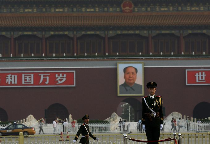 With a backdrop of a portrait of China's late communist leader Mao Zedong, center, a Chinese paramilitary policeman, right, stands still while another yawns while marching, in Tiananmen Square in Beijing on Friday, June 4, 2010. Chinese authorities tightened security on the vast square during the anniversary of the deadly 1989 crackdown on pro-democracy protestors, which was marked Friday. (AP Photo/Muhammed Muheisen)