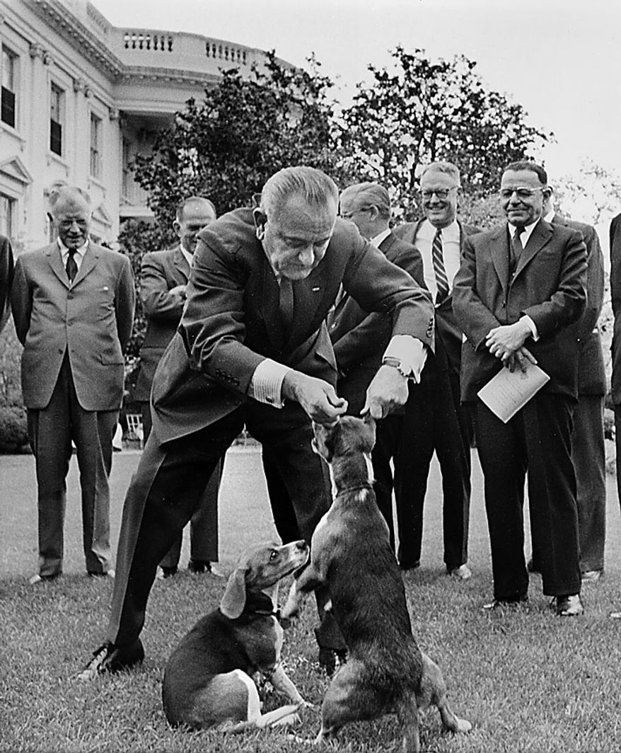"President Lyndon B. Johnson holds his dog ""Her"" by the ears as White House visitors look on, April 27, 1964, on the White House lawn in Washington. At left is President Johnson's other dog, ""Him.""  This picture raised criticism from dog lovers. (AP Photo/Charles P. Gorry)"