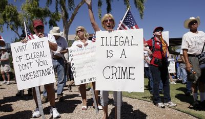 **FILE** Judy Schulz (front) and her husband, Richard Schulz (left), both of Glendale, Ariz., joined hundreds on June 5, 2010, for a rally near the capitol in Phoenix supporting Arizona's new law on illegal immigration. (Associated Press/Ross D. Franklin)