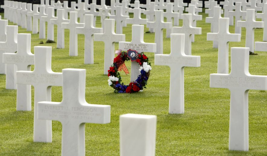 A wreath marks the grave of U.S. soldier Edward M. Withers of Wisconsin at the Colleville U.S. cemetery in northwestern France's Normandy region on Sunday, June 6, 2010, the 66th anniversary of D-Day. (AP Photo/Remy de la Mauviniere)