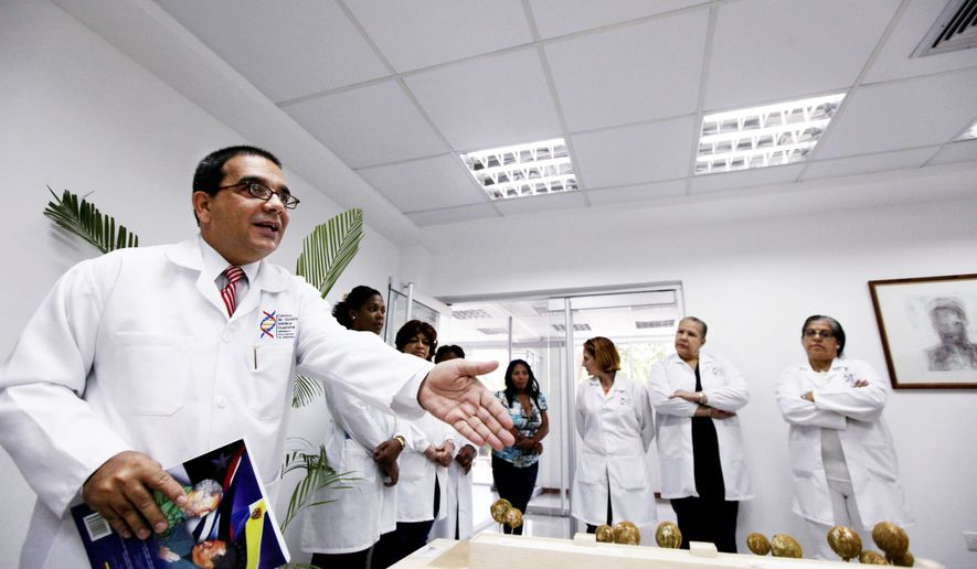 "Dr. Reinaldo Menendez of Cuba directs staff members at the National Genetic Medicine Center near Caracas, Venezuela, which also employs Venezuelans. ""What we came to do is science,"" said Dr. Menendez. ""Our weapons ... are our minds, our work, our coats, our stethoscopes. (Associated Press)"