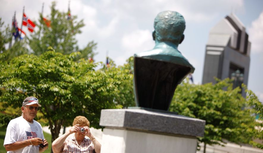 Wayburn Norfleet and Norma Stover, visiting from Indiana, take pictures of the Josef Stalin bust at National D-Day Memorial in Bedford, Va. The controversial bust was installed in time for Sunday's 66th anniversary of the World War II invasion of Normandy. (Associated Press)