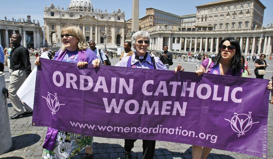 Representatives of the Women's Ordination Conference stage a protest in front of St. Peter's Basilica at the Vatican on Tuesday, June 8, 2010. Holding a poster are (from left) Therese Koturbash of Dauphin, Manitoba; Mary Ann Schoettly of Newton, N.J; and Erin Saiz Hanna of Washington. (AP Photo/Pier Paolo Cito)