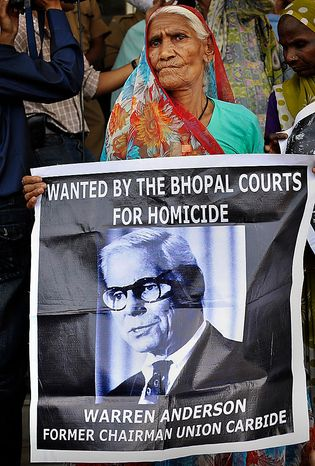 """An elderly survivor holds a poster of Warren Anderson, the head of Union Carbide Corp. at the time of the gas leak, as she waits for the verdict in the premises of Bhopal court in Bhopal, India, on June 7, 2010. The court convicted seven former senior employees of Union Carbide's Indian subsidiary of """"death by negligence"""" for their roles in the Bhopal gas tragedy that left an estimated 15,000 people dead more than a quarter century ago in the world's worst industrial disaster. (Associated Press)"""