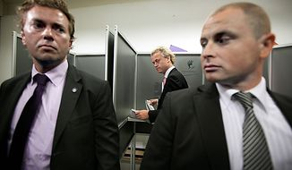 ** FILE ** Flanked by two bodyguards, populist anti-Islam leader Geert Wilders (center) prepares to cast his ballot in The Hague on June 9, 2010. (Associated Press)