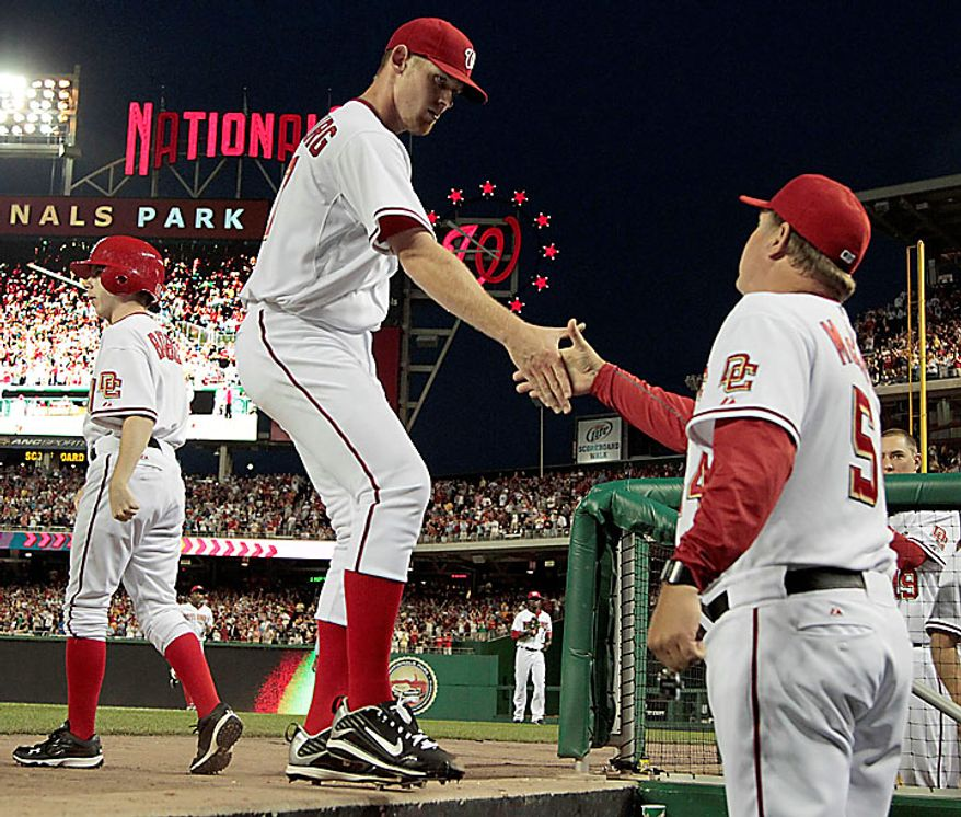 Washington Nationals starting pitcher Stephen Strasburg is met by pitching coach Steve McCatty as he walks off the field in the seventh inning after 14 strikeouts in his major league debut, during the baseball game against the Pittsburgh Pirates in Washington, Tuesday, June 8, 2010. (AP Photo/Manuel Balce Ceneta)
