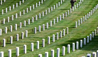 "Army Spc. Matthew Burt, 25, of Titusville, Penn., with the 3rd U.S. Infantry Regiment, known as ""the Old Guard,"" places flags on the graves at Arlington National Cemetery in Arlington, Va., on May 27. At least 211 remains were identified as potentially mislabeled or misplaced. (Associated Press photographers)"