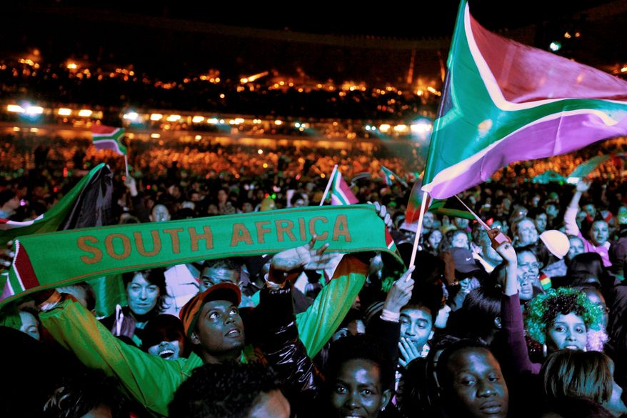 ** FILE ** Spectators wave their national flags during the opening concert for the World Cup at Orlando Stadium in Soweto, South Africa, last Thursday. (Associated Press)