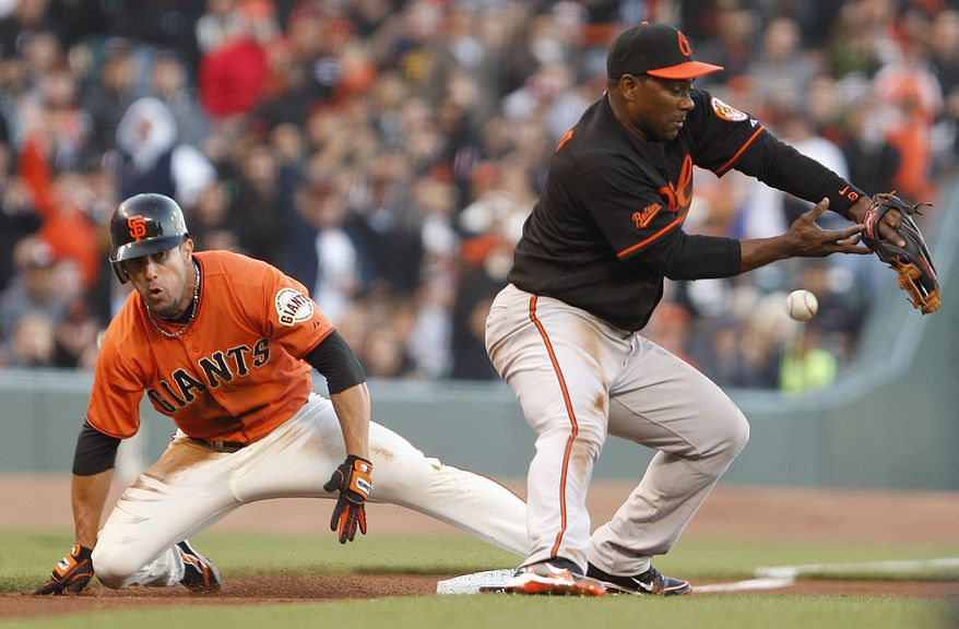 ASSOCIATED PRESS San Francisco Giants' Andres Torres, left, slides safely past Baltimore Orioles third baseman Miguel Tejada with a triple during the first inning of a baseball game Monday, June 14, 2010, in San Francisco.