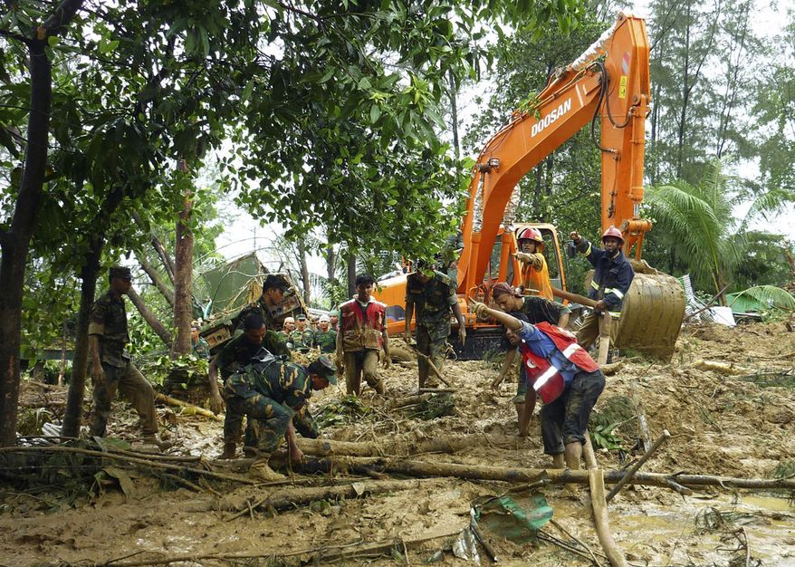 Bangladeshi army personnel clear the area after landslides struck in the southern coastal area of Cox's Bazar, 185 miles south of Dhaka, Bangladesh, on Tuesday, June 15, 2010. The powerful landslides, triggered by heavy rains from a depression in the Bay of Bengal, killed at least 47 people. (AP Photo/Tofayel Ahmed)