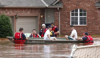 An Oklahoma City Fire Department rescue crew takes two boys and their dog to high ground in Edmond, Okla., after flood waters inundated a number of homes in the area on Monday, June 14, 2010. (AP Photo/The Oklahoman, Paul Hellstern)