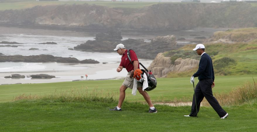 Tiger Woods walks down the 10th fairway with his caddie, Steve Williams, during a practice round for the U.S. Open golf tournament in Pebble Beach, Calif., Monday, June 14, 2010. (AP Photo/Charlie Riedel)