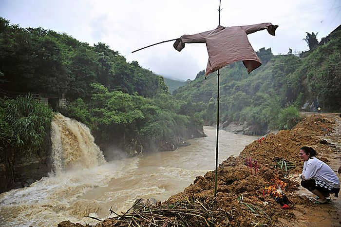 A Chinese woman mourns a family member killed by flash floods in Nanping, in eastern China's Fujian Province,  on Tuesday, June 15, 2010. Dozens of people are missing after flash floods and landslides triggered by heavy rains engulfed two vehicles in Fujian, according to state media. (AP Photo)