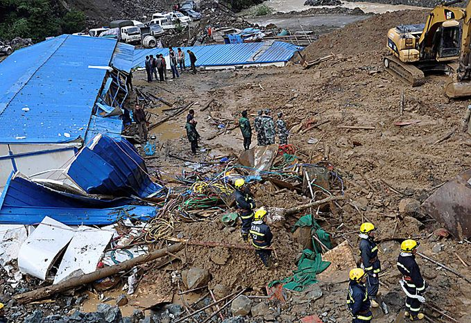 Rescuers work at the site of a massive landslide triggered by heavy rains in Pengta Town, Kangding County, Ganzi Tibetan Autonomous Prefecture in southwest China's Sichuan province on Tuesday, June 15, 2010. The landslide occurred at a construction site of a hydroelectric dam early Tuesday morning after heavy rains, the official Xinhua News Agency reported. It said workers were killed and  wounded when part of a mountain gave way and buried the site. Four workers managed to escape unharmed. (AP Photo)