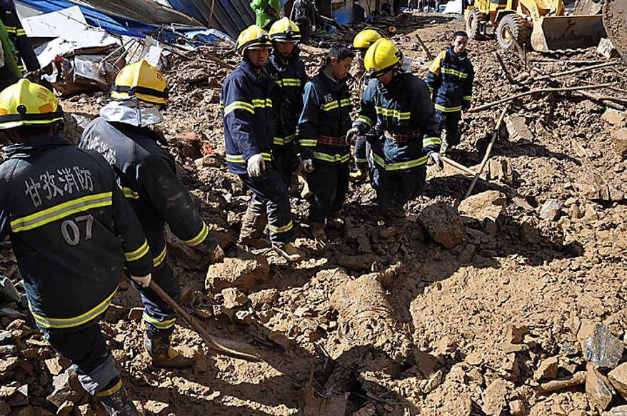 Rescuer workers find a body covered in mud at the site of a massive landslide triggered by heavy rains in Pengta Town, Kangding County, Ganzi Tibetan Autonomous Prefecture in southwest China's Sichuan province on Tuesday, June 15, 2010. The landslide occurred at a construction site of a hydroelectric dam early Tuesday morning after heavy rains, the official Xinhua News Agency reported. It said 23 workers were killed and seven wounded when part of a mountain gave way and buried the site. Four workers managed to escape unharmed. (AP Photo)
