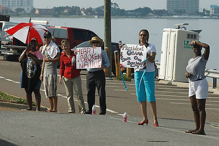 Bystanders watch the motorcade carrying President Obama and Florida Gov. Charlie Crist along Casino Beach on Pensacola Beach, Fla., Tuesday, June 15, 20010, as they visited the Gulf Coast region affected by the BP Deepwater Horizon oil spill. (AP Photo/Charles Dharapak)