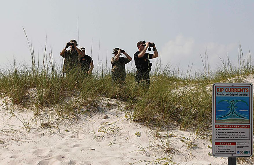 Security personnel stand watch as President Obama and Florida Gov. Charlie Crist walk along Casino Beach on Pensacola Beach, Fla., Tuesday, June 15, 20010, as they visited the Gulf Coast region affected by the BP Deepwater Horizon oil spill. (AP Photo/Charles Dharapak)