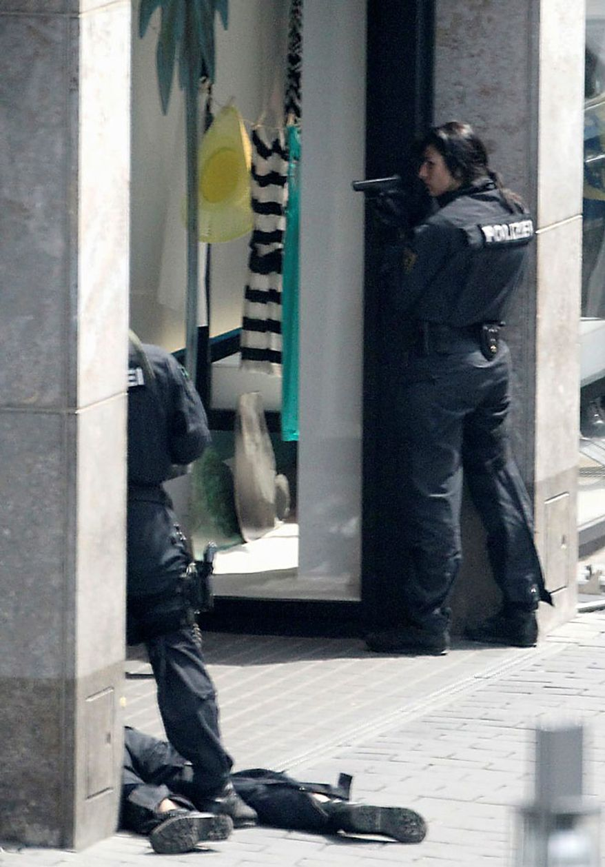 Police officers secure the exterior of an H&M clothing store in central Leipzig, Germany, on Tuesday, June 15, 2010, as an armed man inside holds several hostages, who were released without injury several hours later. Police spokeswoman Uta Barthel told the Associated Press that a 41-year-old man was in custody and that authorities believe psychological problems led to the hostage-taking. She declined to say how many hostages were taken, but said all were being cared for by medical professionals. (AP Photo/ddp/Sebastian Willnow)