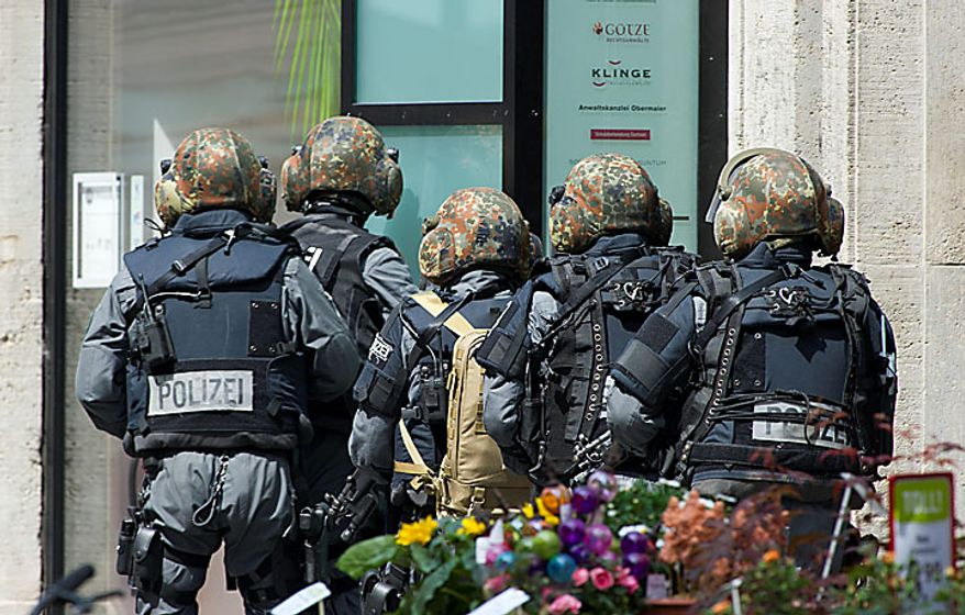 Police officers secure the exterior of an H&M fashion store in central Leipzig, Germany, on Tuesday, June 15, 2010, as an armed man inside holds several hostages, who were released without injury several hours later. Police spokeswoman Uta Barthel told the Associated Press that a 41-year-old man was in custody and that authorities believe psychological problems led to the hostage-taking. She declined to say how many hostages were taken, but said all were being cared for by medical professionals. (AP Photo/dapd/Eckehard Schulz)
