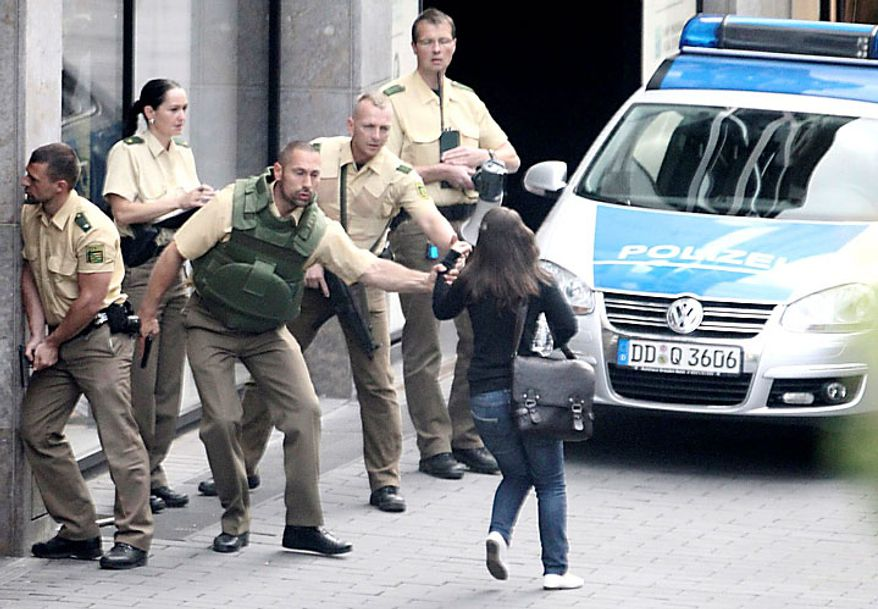 Police officers outside an H&M fashion store in central Leipzig, Germany, try to secure a pedestrian on Tuesday, June 15, 2010, as an armed man inside holds several hostages, who were released without injury several hours later. Police spokeswoman Uta Barthel told the Associated Press that a 41-year-old man was in custody and that authorities believe psychological problems led to the hostage-taking. She declined to say how many hostages were taken, but said all were being cared for by medical professionals. (AP Photo/ddp/Sebastian Willnow)