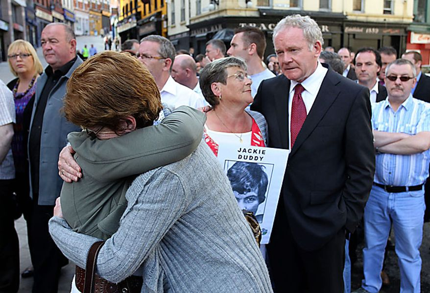 Relatives comfort each other as Kay Duddy, brother of Jackie Duddy, who was shot dead on Bloody Sunday, talks with Northern Ireland Deputy First Minister Martin Mc Guinness (right) in Londonderry, Northern Ireland, on Tuesday, June 15, 2010. Relatives and family members of the dead made their way to the Guildhall to receive a preview of the Saville Report, which details the British government's findings from the investigation into Bloody Sunday, the 1972 killing of 13 Catholic demonstrators by British troops. The probe began in 1998 and became the most expensive in British legal history as it gathered evidence from 2,500 witnesses, including troops who opened fire that day.  (AP Photo/Peter Morrison)