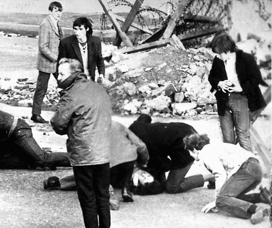 In this Sunday, Jan. 31, 1972, photo, a man receives attention during the shooting incident in Londonderry, Northern Ireland, that became known as Bloody Sunday. An epic 12-year investigation into Northern Ireland's biggest mass killing by British soldiers reached a bittersweet climax on Tuesday, June 15, 2010, as relatives of the 13 Catholic demonstrators killed that day began reading a 5,000-page report into why the 1972 slaughter happened. (AP Photo/ PA/File)