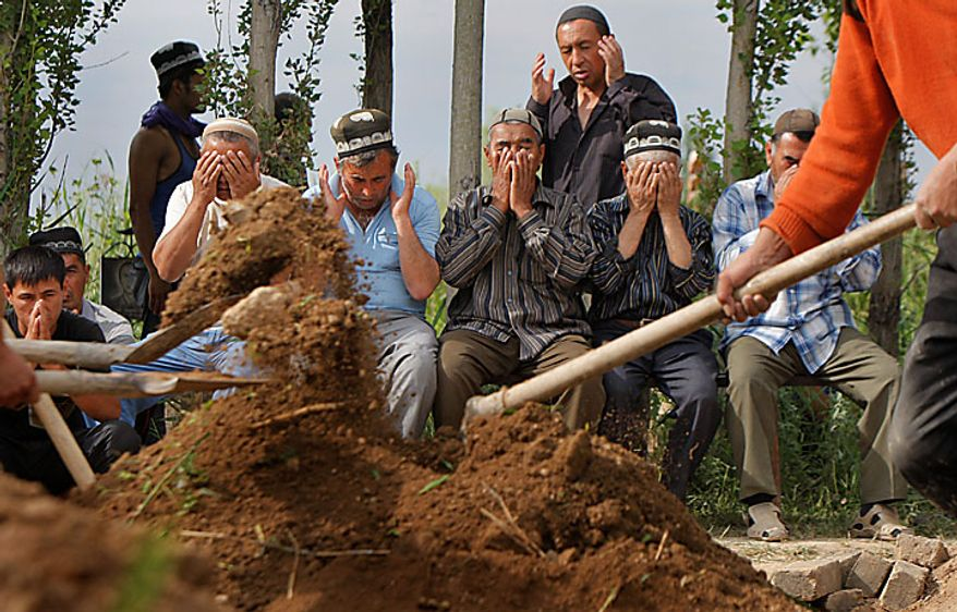Uzbek men pray in the southern Kyrgyz city of Osh on Tuesday, June 15, 2010, during the funeral of a victim of ethnic rioting between Kyrgyz and ethnic Uzbeks. The rioting has killed at least several hundred people, or roughly double official figures, the Red Cross said Tuesday as new reports strengthened suspicions that the rioting in Kyrgyzstan was started deliberately. (AP Photo/Sergei Grits)