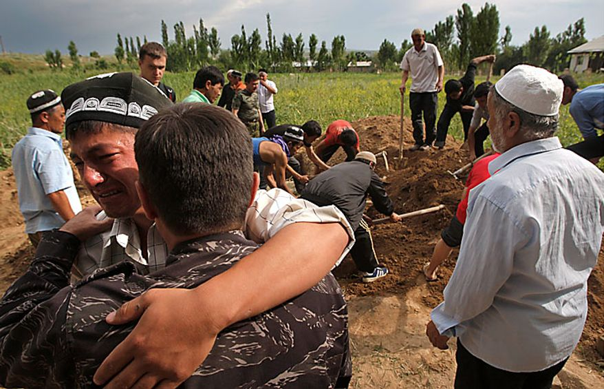 In the southern Kyrgyz city of Osh, Uzbek men mourn on Tuesday, June 15, 2010, during the funeral of a victim of ethnic rioting between Kyrgyz and ethnic Uzbeks. Rioting has killed at least several hundred people, or roughly double official figures, the Red Cross said Tuesday, as new reports strengthened suspicions that the rioting in Kyrgyzstan was started deliberately. (AP Photo/Sergei Grits)