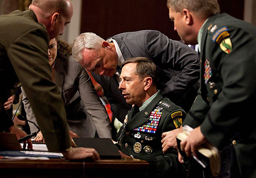 Army Gen. David Petraeus, U.S. Central commander, is surrounded by staff after appearing to collapse on Capitol Hill in Washington on Tuesday, June 15, 2010, while testifing before the Senate Armed Services Committee. (AP Photo/Evan Vucci)