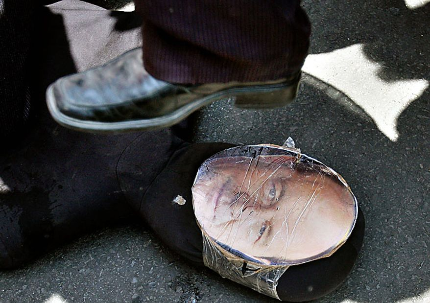 A protester steps on an effigy depicting Romanian President Traian Basescu during a protest in Bucharest Tuesday, June 15, 2010. Thousands of angry Romanians protested Tuesday outside parliament against salary and pension cuts as the legislature started debating a no-confidence motion in the government.(AP Photo/Vadim Ghirda)