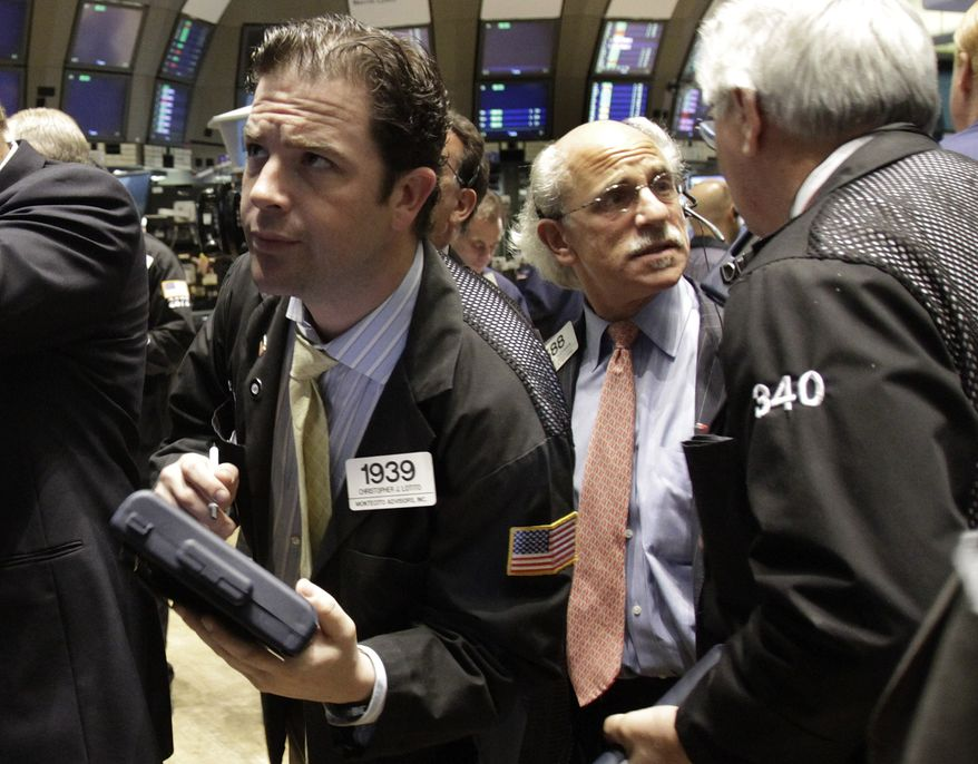 Trader Christopher Lotito, left, checks prices as he works on the floor of the New York Stock Exchange on Wednesday, June 16, 2010. (AP Photo/Richard Drew)