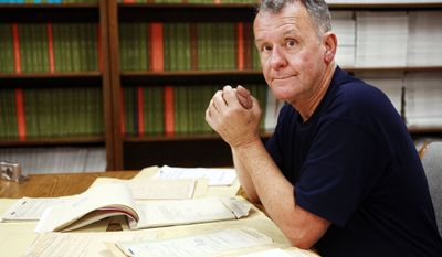 In this photo taken Tuesday, June 8, 2010, Ted Darcy, of Fall River, Mass., is surrounded by documents on his research into the identity of soldiers missing in action from WWII, while at the National Records Center in Suitland, Md. (AP Photo/Jacquelyn Martin)